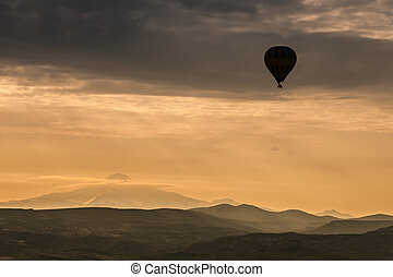 Hot air balloon during sunrise - Hot air balloon is flying...