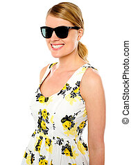 Smiling young woman wearing sunglasses over white background