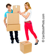 Young couple holding and moving boxes - American woman...