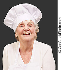 senior cook woman smiling over black background