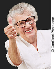 portrait of adorable senior woman doing good gesture over...