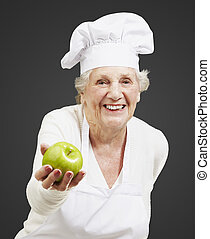 senior woman cook offering a green apple against a black...