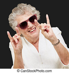 portrait of a happy senior woman doing rock symbol over...