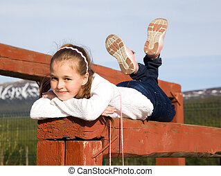 A girl lies on the balance beam and smiling - A girl lies on...