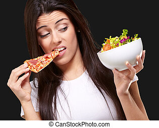 portrait of young woman eating pizza and looking salad over black