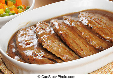 Serving dish of salisbury steak - Close up of a serving dish...