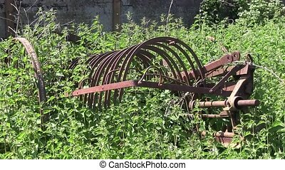 Old and rusty hay rake that is overgrown with weeds an...