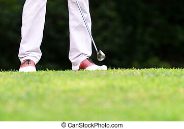Legs of golfer who  hitting a driver from the tee-box