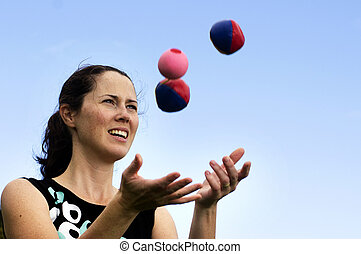 Woman Juggling Balls - Young woman juggler is juggling balls...