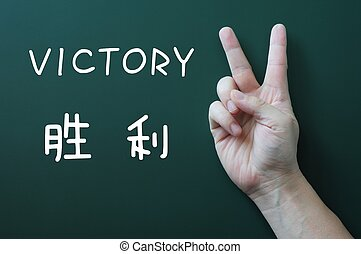 Victory gesture on a blackboard background, with the word...