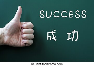 Success written on a blackboard with a thumb up - Success...