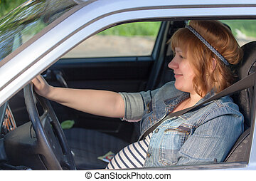 Pregnant woman fastening seat belt in the car