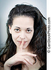 Sensual young woman with her finger on her lips