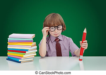 Boy genius with books and large pencil adjusting his glasses...