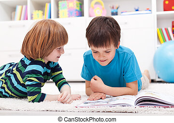 Young boys reading story book laying on the floor