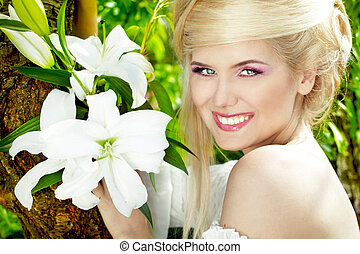 Happy Smiling blonde young woman with white lily, nature