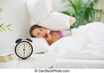 Upset woman closing ears by pillow to avoid hearing alarm...