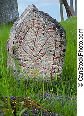 Rune stone - Swedish old rune stone in green grass