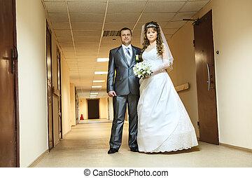 Young wedding Caucasian Russian couple standing in long corridor