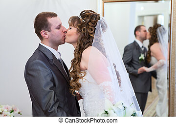 Young wedding Caucasian Russian couple kissing together. Reflection in mirror