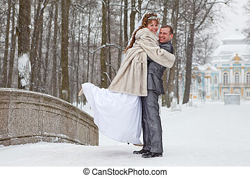 Young wedding Caucasian Russian couple embracing on snowy park. Winter season in Russia