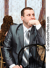 Tired Caucasian Russian bridegroom waiting for bride during...