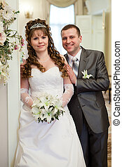 Happy Caucasian newlywed couple standing together. White dress and grey siut. Bunch of lilies in hands