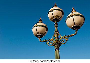Antique lamp post - green vintage lamp posts against a blue...