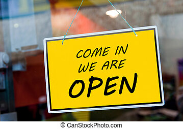 Open sign - come in we are open sign hanging on a window...