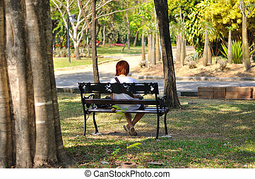 Woman siting on bench in park