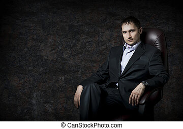 Young adult handsome man sitting in leather armchair