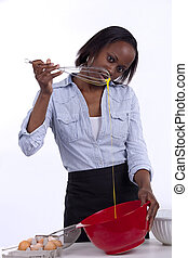 Young woman beating an egg with a whisk and checking consistency.