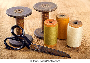 Scissors and spools  on wooden background