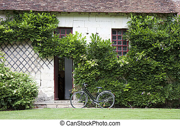 bike near the entrance in a traditional house, France -...
