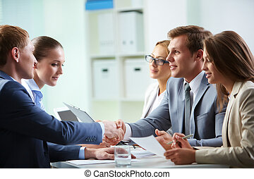 Agreement - Image of confident businessmen handshaking at...