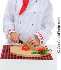 Chef cuts the tomato - Chef in uniform cuts the tomato in...