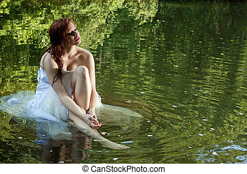 A beautiful bride sitting in water