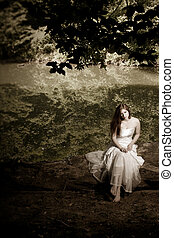 Woman sitting on a log, desaturated - A woman or bride...