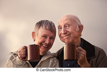Smiling Senior Couple Toasting with Mugs - Satisfied senior...