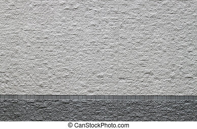 A two style gray rock brick wall of the side of a building...