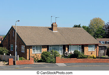 English bungalow houses with flowery gardens in summer.