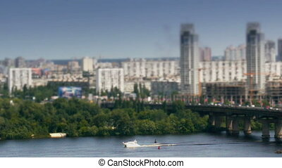 Motor boat on river and car traffic on bridge in Kiev timelapse