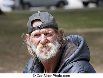 Homeless man sitting outdoors during the day