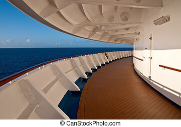 Promenade deck of a cruise ship with sea and sky. There are...