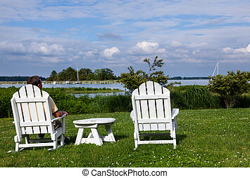 Single senior man in white chairs overlooking bay - Patio...