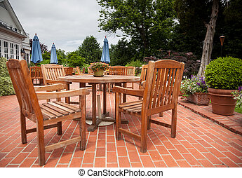 Teak patio tables and chairs on brick deck - Many wooden...