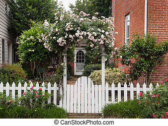 Wild flowers growing over white picket fence - Yellow and...