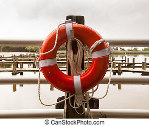 Red life belt in front of empty boat dock harbor - Lone red...