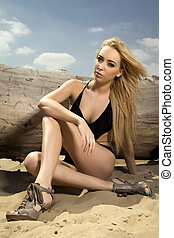 beautiful blonde woman in black swimwear posing on a log