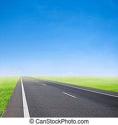 car road over blue sky - green field and car road over blue...